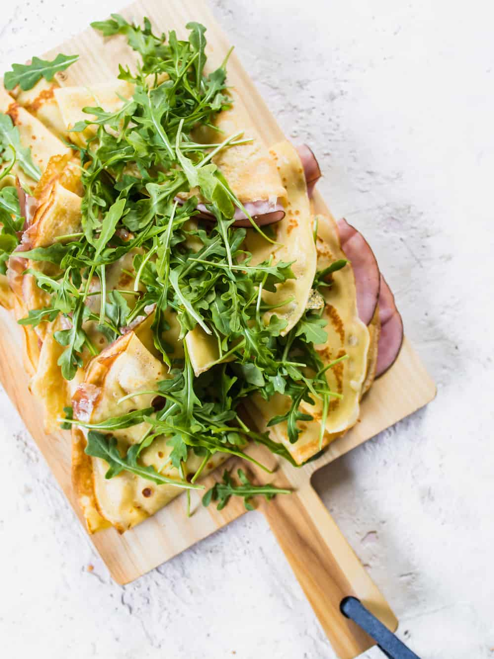 Cooked crepes with ham and topped with fresh arugula.