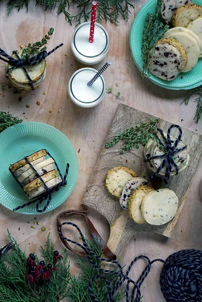 cookies stacked and wrapped with string, 2 green plates and milk.