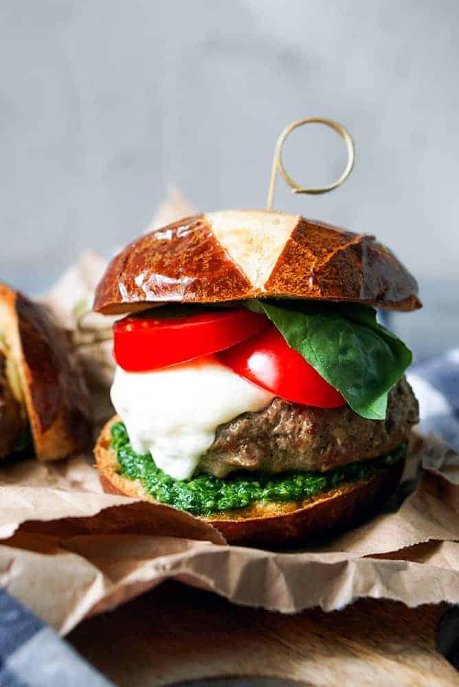 Close up of a caprese salad burger on a pretzel bun