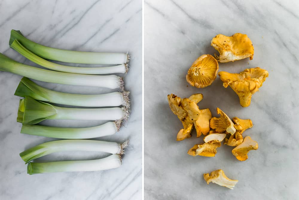Raw leeks in a line and a bunch of chanterelle mushrooms on the right