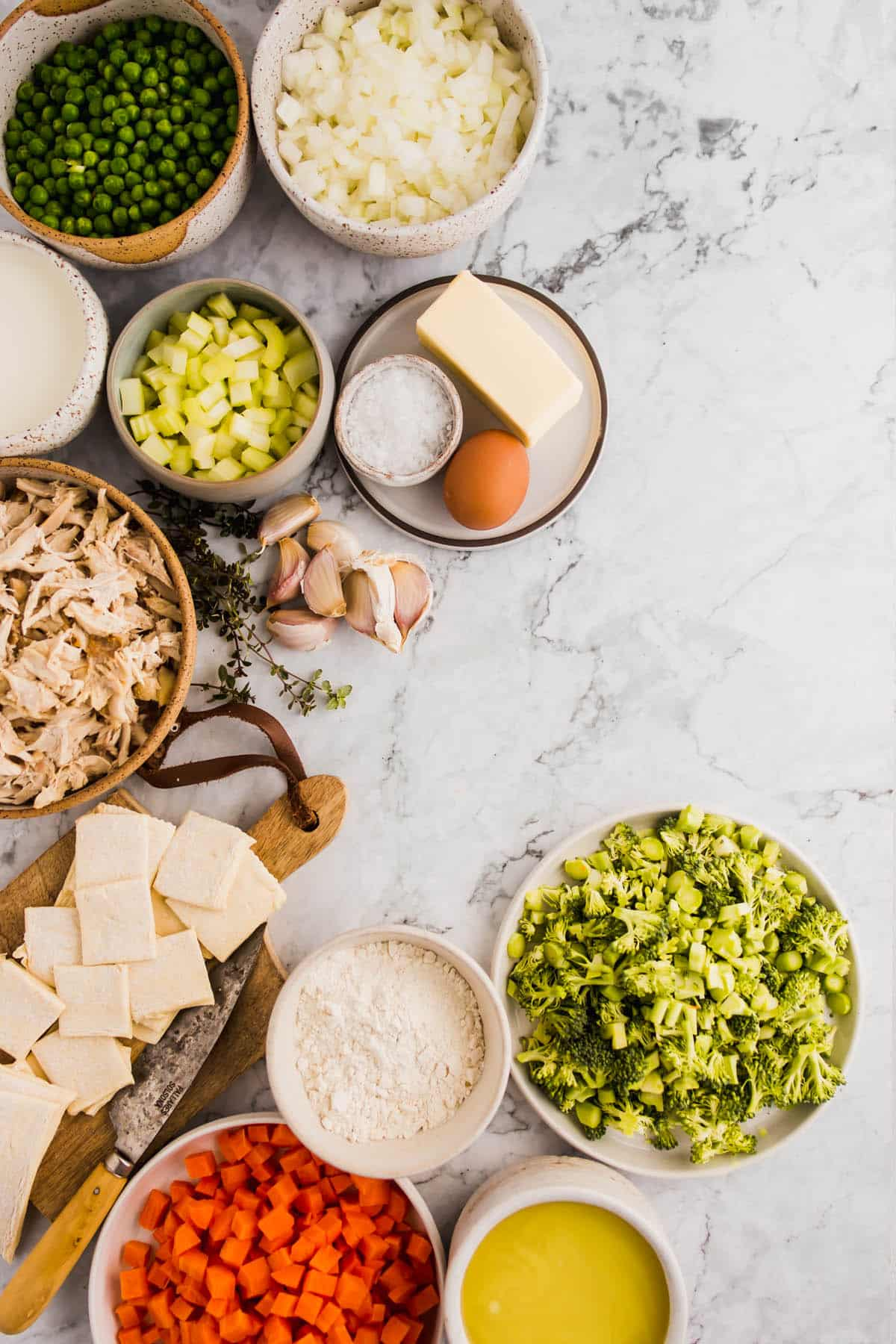 Ingredients for Quick and Easy Homemade Chicken Pot Pies with Puff Pastry. Using peas, onion, celery, salt, butter, egg wash, garlic, thyme, chicken, milk, brocolli, puff pastry, chicken stock, carrots, and flour.