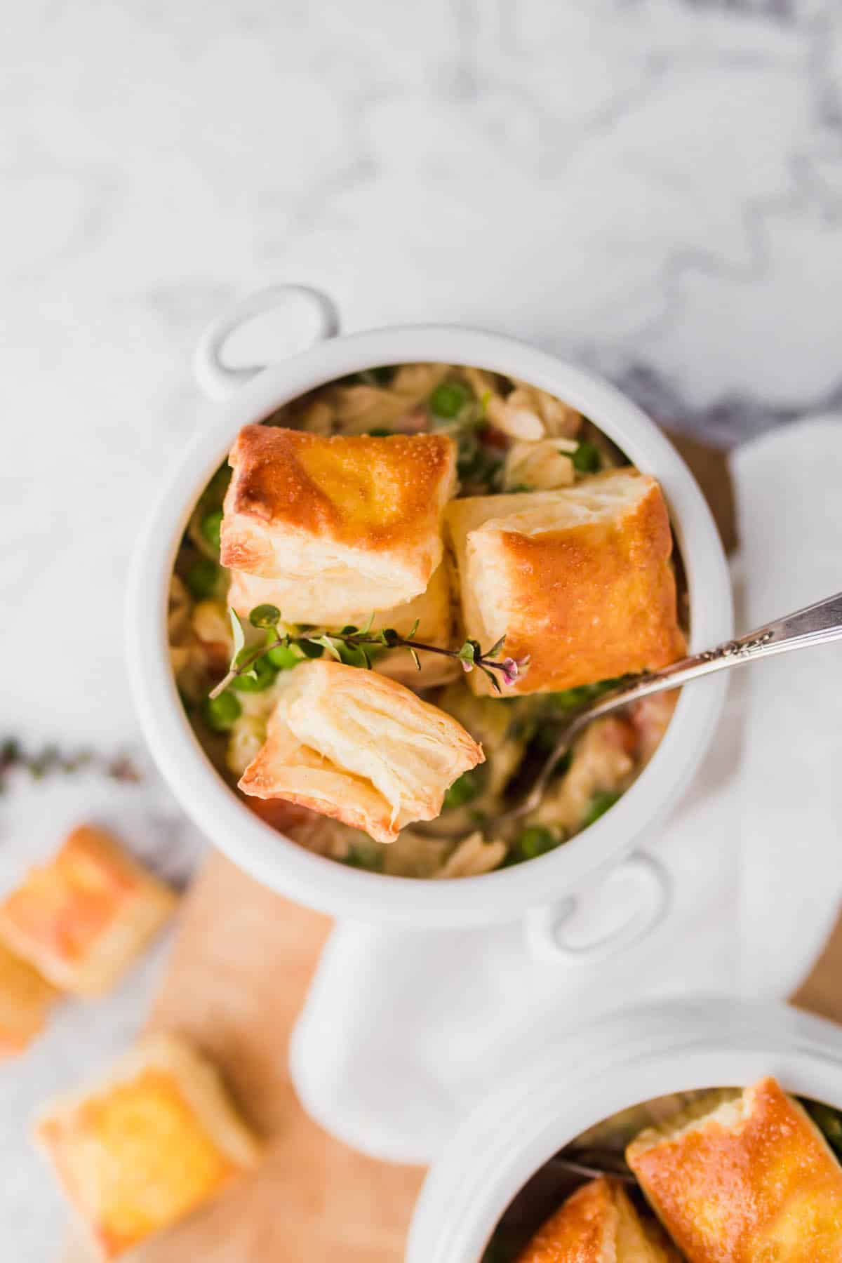 Quick and Easy Homemade Chicken Pot Pies with Puff Pastry served in a white bowl with fresh thyme.