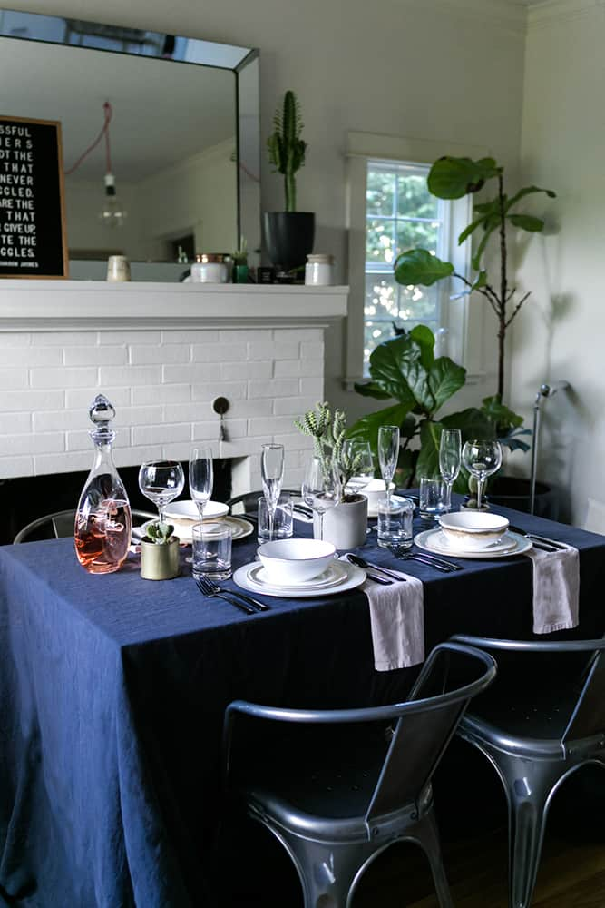 Table set with dark blue linen, chairs, wine, glasses, plates and bowls