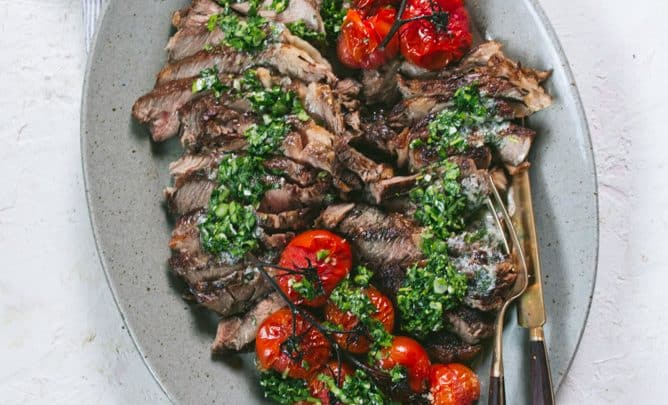 delicious ribeye steak with chimichurri sauce and roasted tomatoes