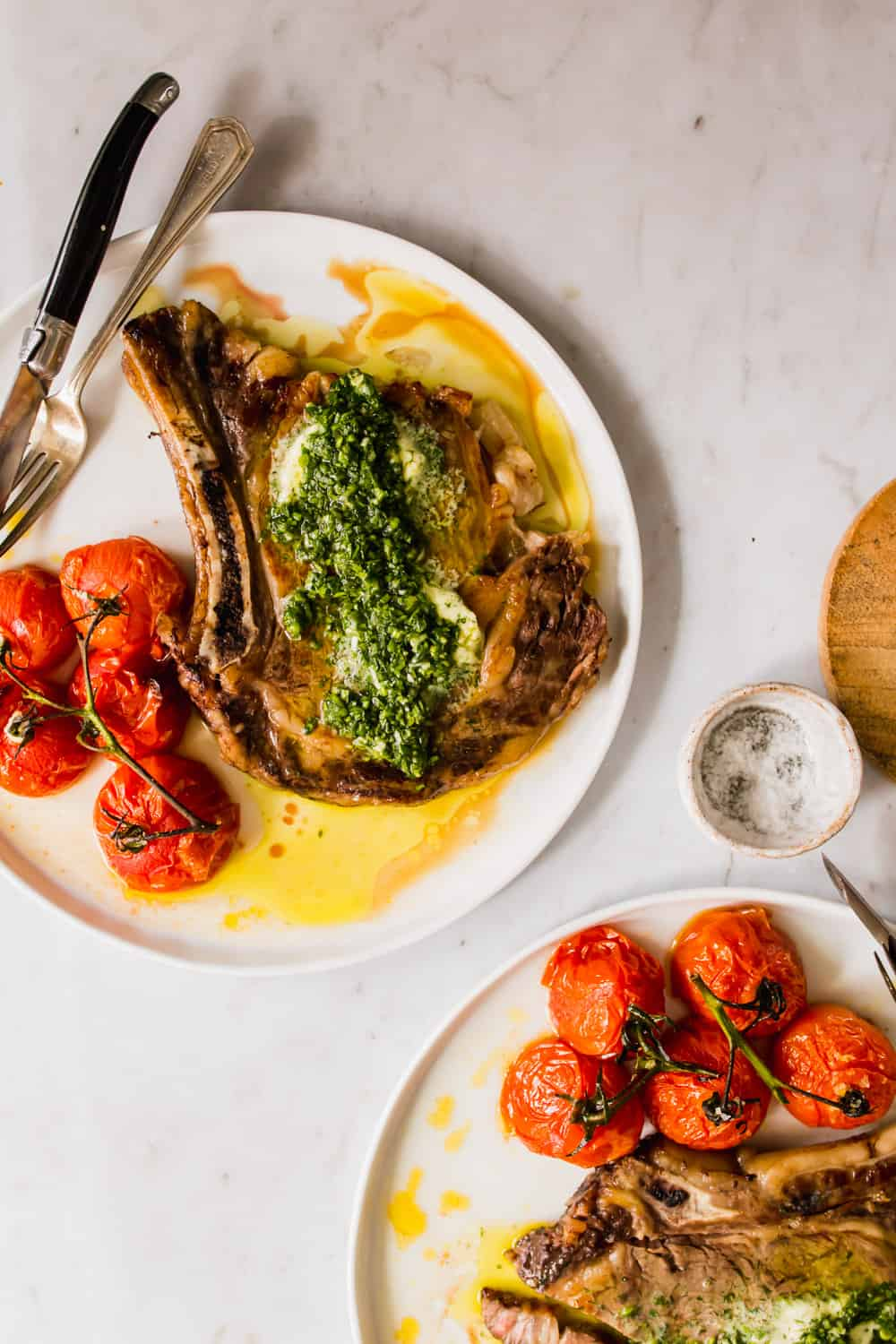 2 white plates holding steak and roasted tomatoes