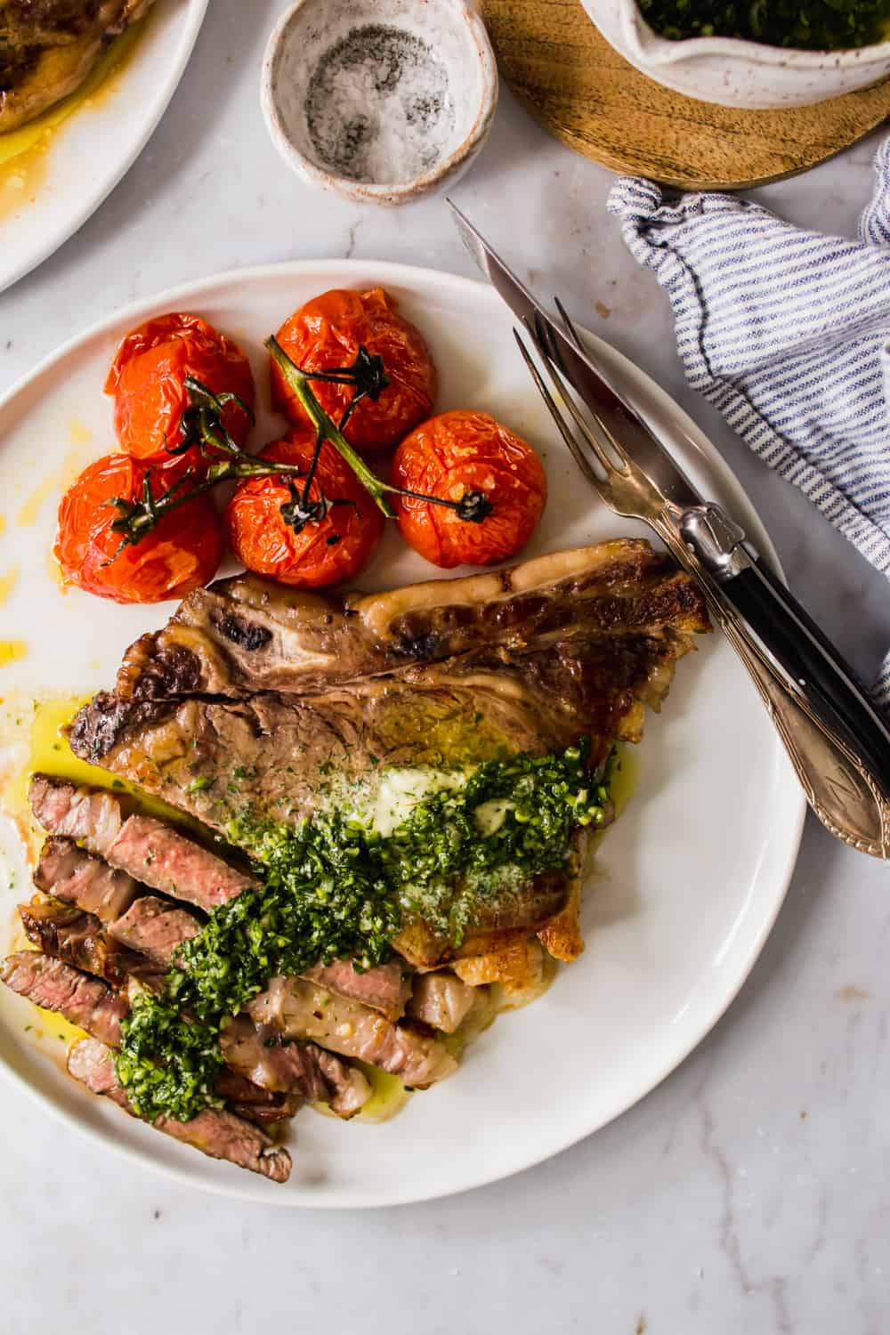 sliced steak on a white plate with green sauce on top and roasted tomatoes on the side