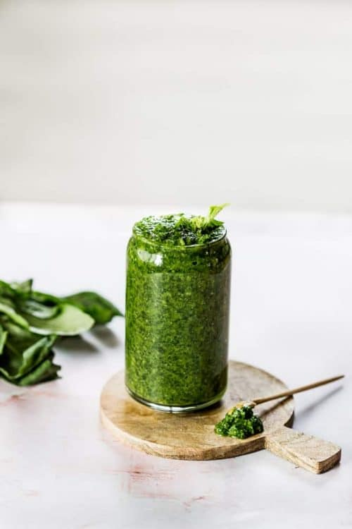 arugula basil pesto in glass with spoon and small wood board