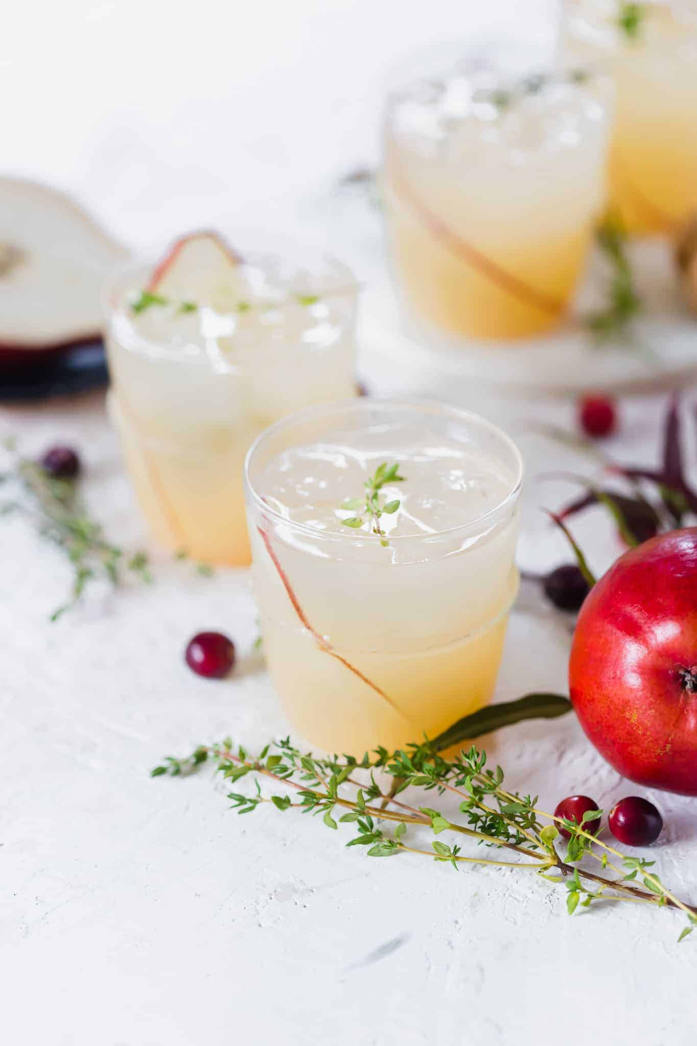 This Fizzy Pear Cocktail combines the flavors of rich pear, earthy thyme, Prosecco and 7UP for a refreshing winter drink. Paired well with Goat Cheese Crostini topped with pear, walnuts and honey. #pearcocktail #cocktail #pear #crostini #appetizer #drink #prosecco