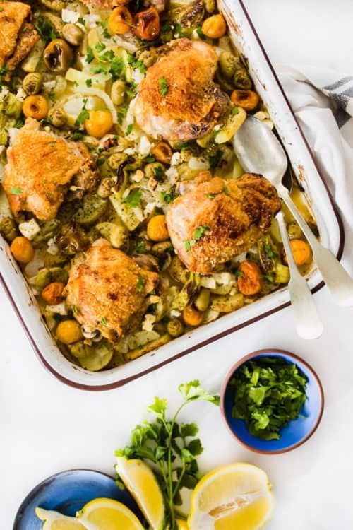 Greek Chicken in one pan with lemons and herbs in blue plates.