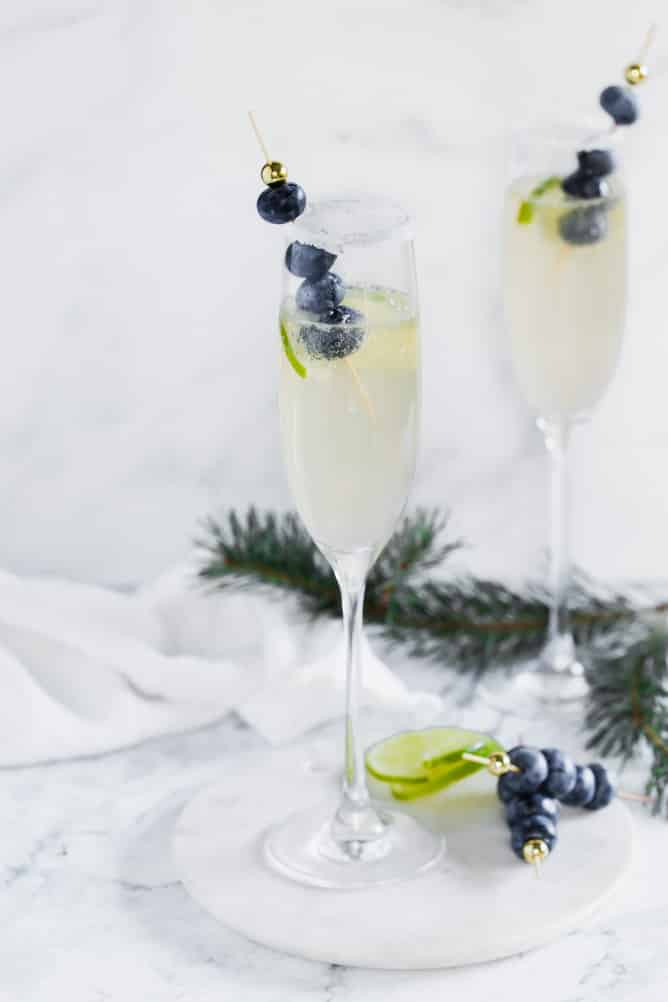 champagne flute with sugar rim, limes and blueberries on a toothpick