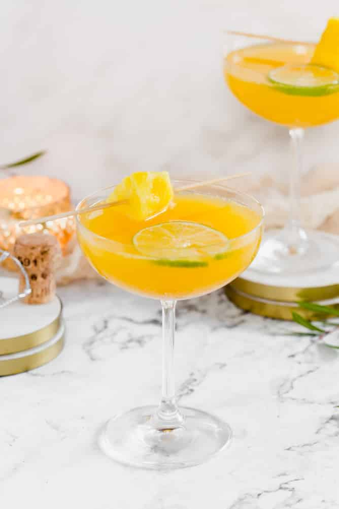 Two champagne glasses filled with orange drinks and coasters.