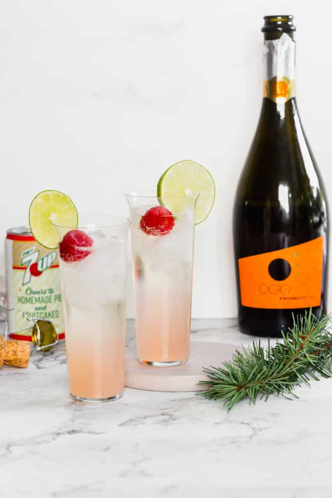 two champagne flutes with raspberry lime mimosas.