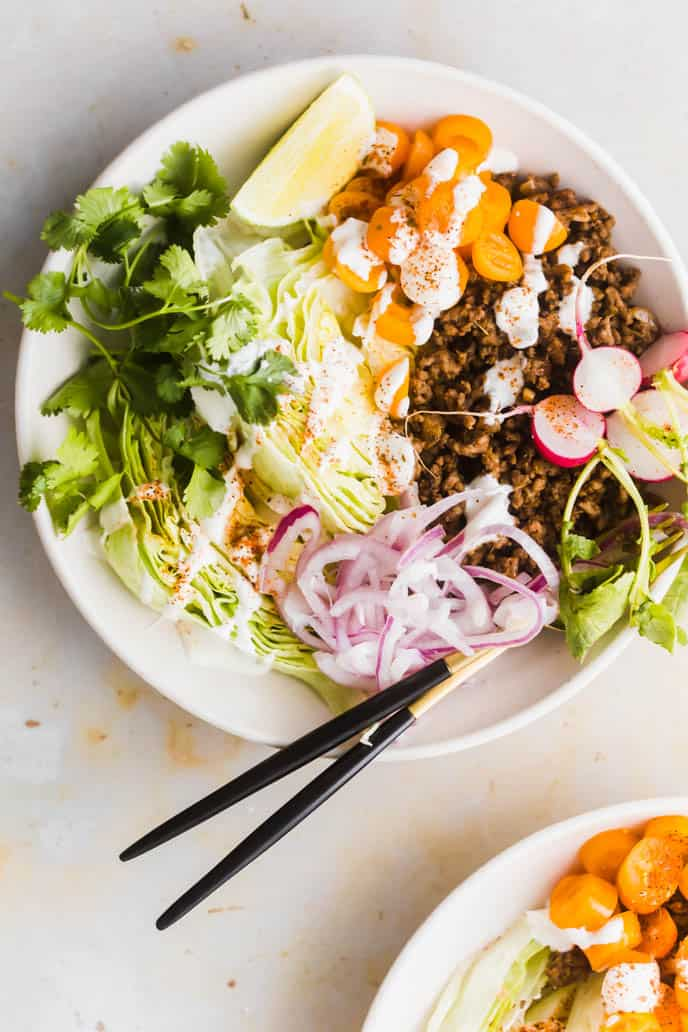 Healthy Taco Bowls With Mexican Beef. Served with yogurt crema, onion, tomatoes, lettuce, lime, radishes, and cilantro.