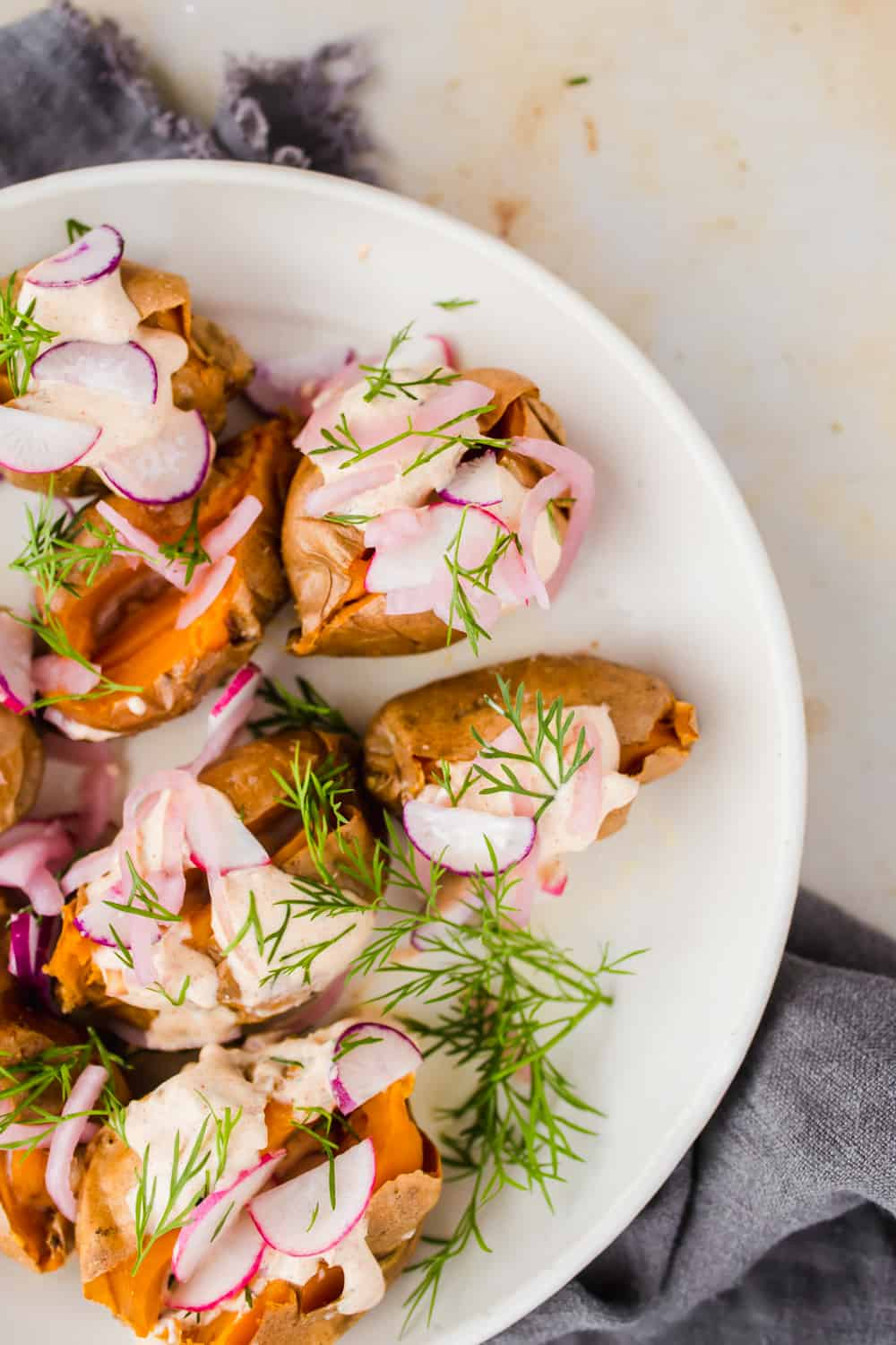 Closeup of Loaded Air Fryer Baked Sweet Potatoes on a white plate with fresh herbs and creamy yogurt sauce.