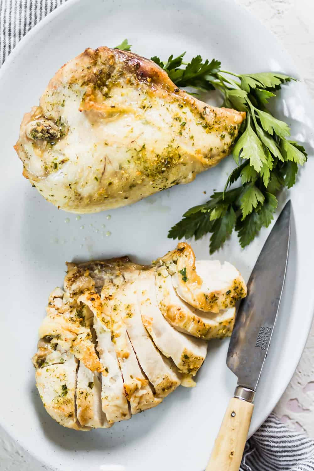 Everyday Baked Chicken Breast sliced and served on a white plate with fresh greens