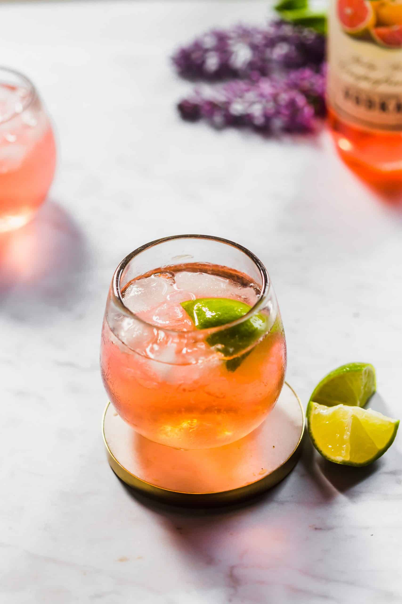 Grapefruit vodka tonic served in a stemless wine glass with ice and a lime wedge.