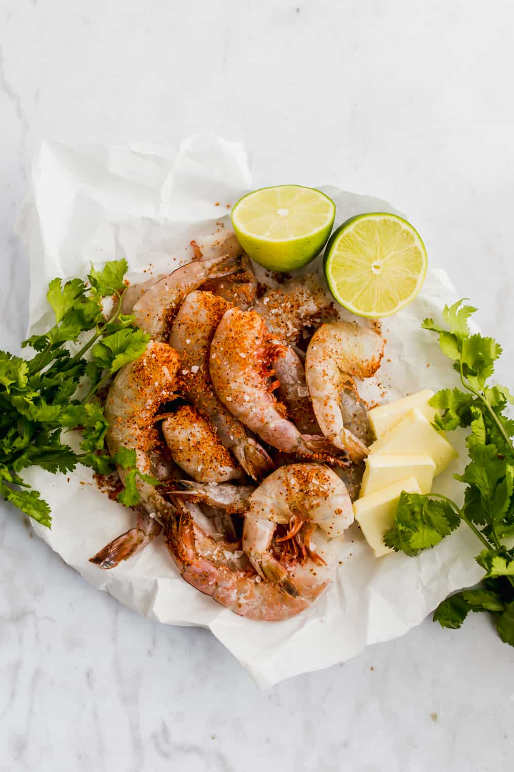 Frozen jumbo shrimp in a bowl with butter, cilantro, lime, and seasoning on top
