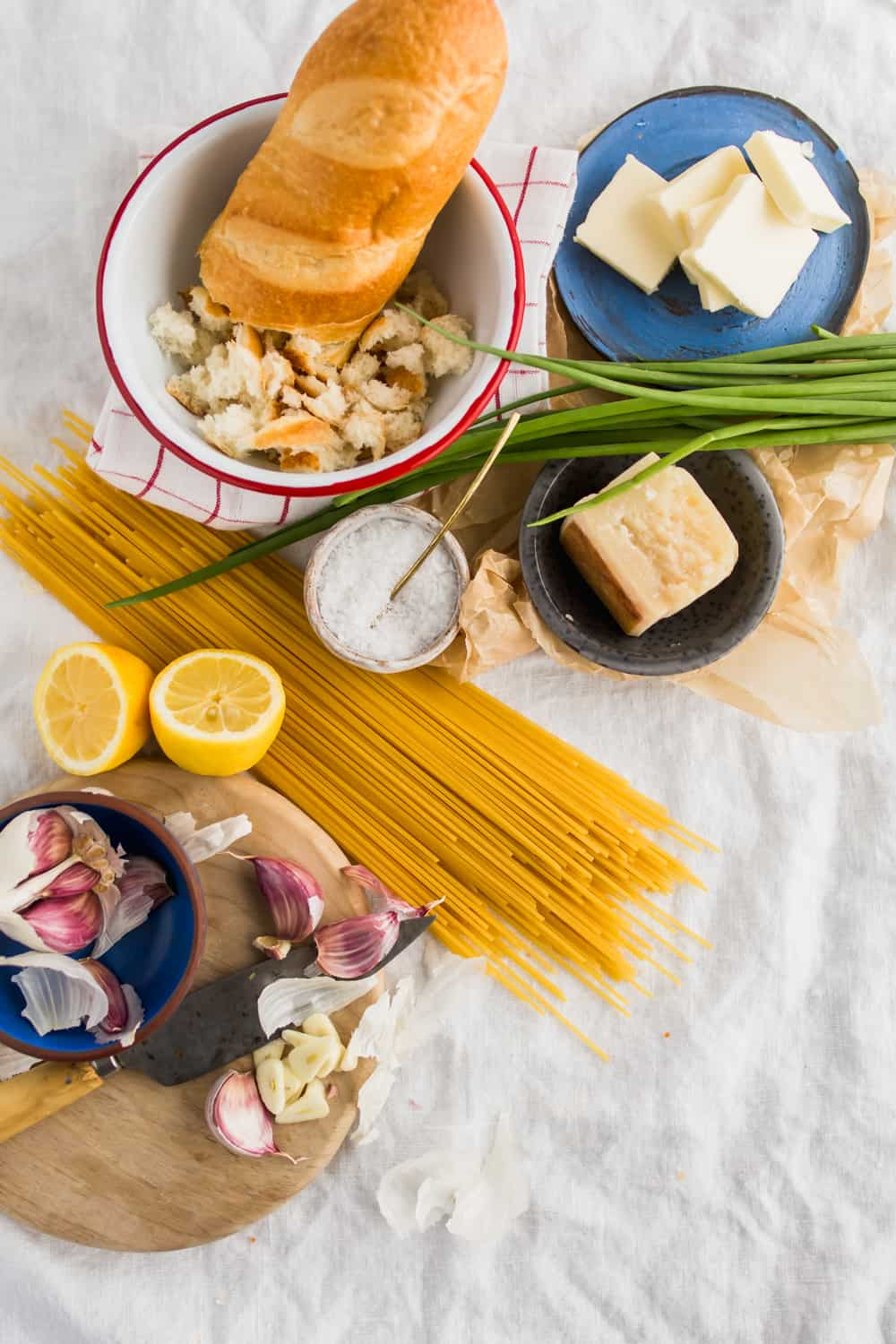Ingredients for the spaghetti with garlic herb breadcrumbs. Fresh bread in a white bowl, butter, fresh parmesan, sea salt, spaghetti, lemon, garlic, and fresh chives.