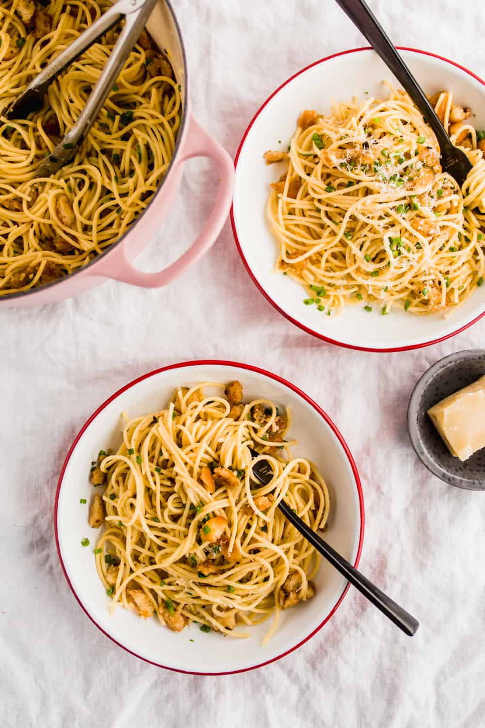 Two servings of Spaghetti with garlic herb breadcrumbs in white bowls. Large pot of spaghetti.