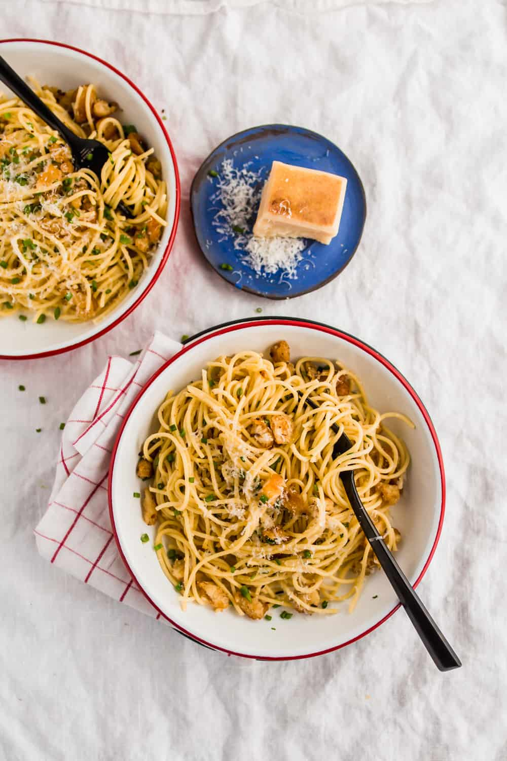 Two servings of Spaghetti with garlic herb breadcrumbs in white bowls and grated parmesan on the side.