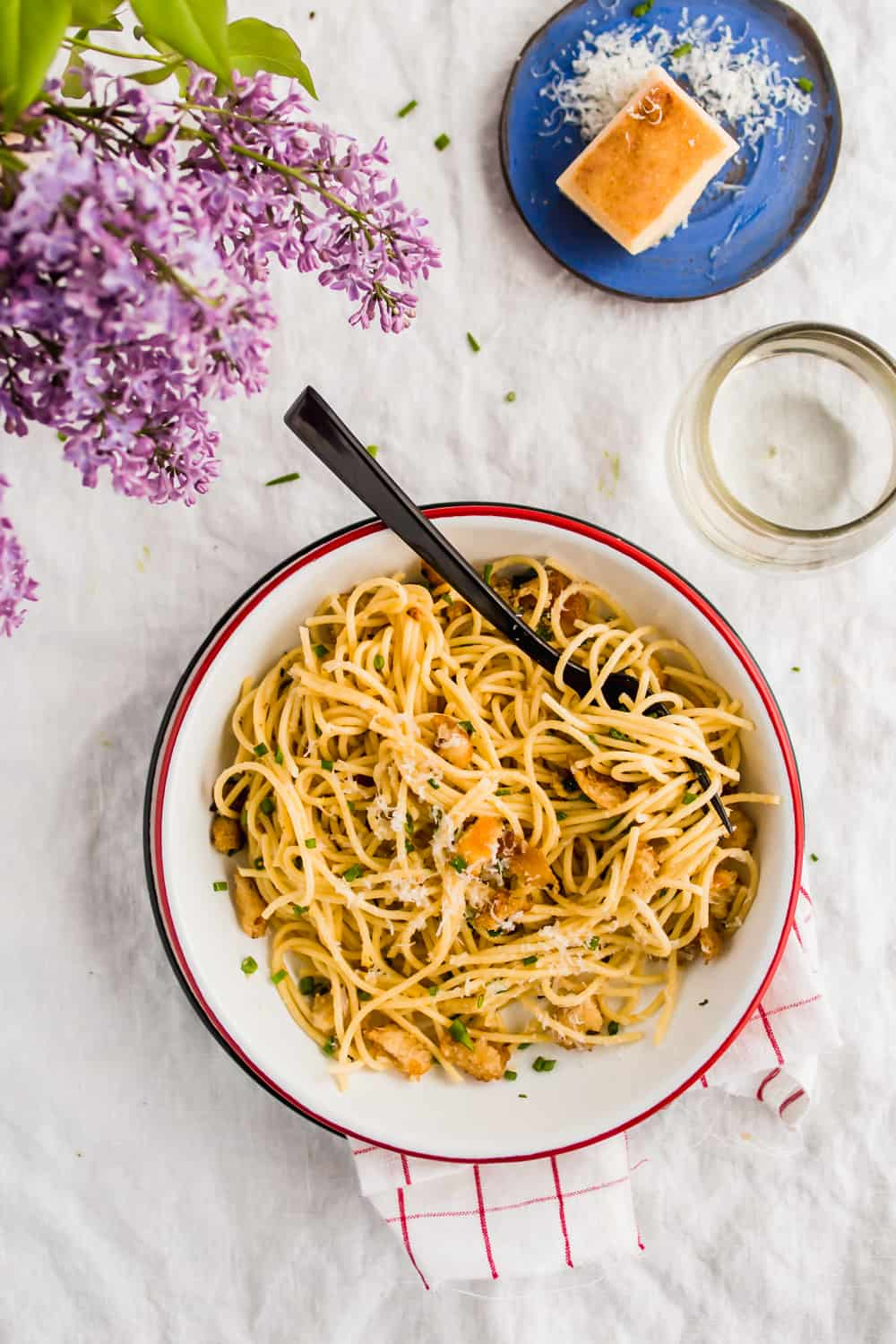 Spaghetti With Garlic Herb Breadcrumbs served in a large white bowl and parmesan on the side.