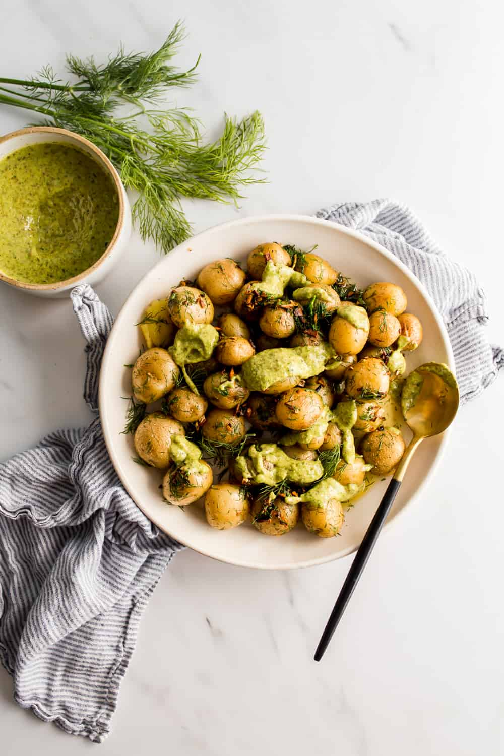 Boiled Baby Potatoes With Garlic Butter And Dill in a white bowl, topped with green tarragon sauce