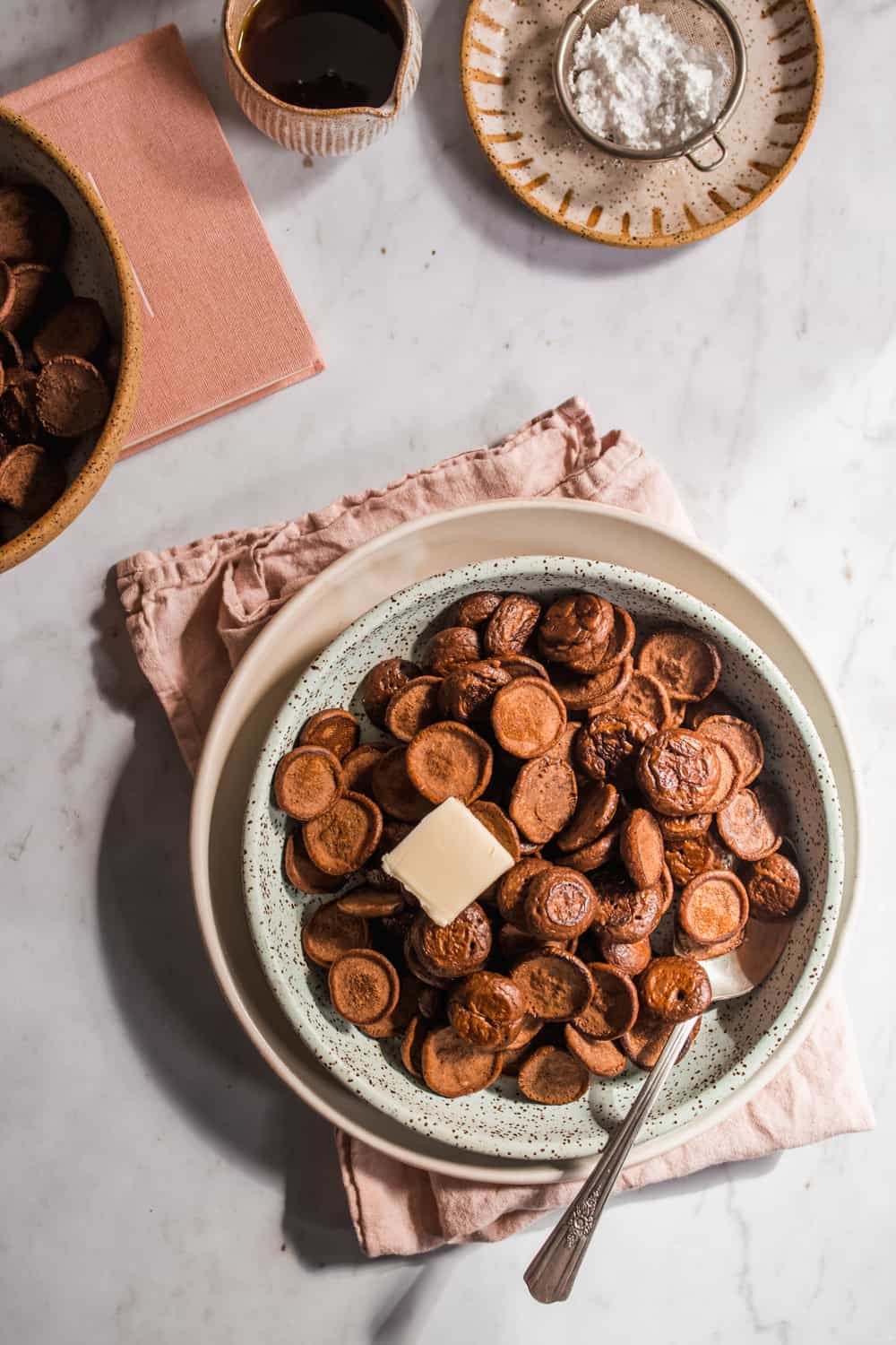 A bowl with the Mini Chocolate Pancake Cereal with butter on top.