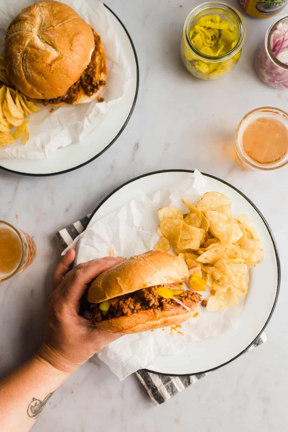 Sloppy joes in a bun on a plate with potato chips on the side.