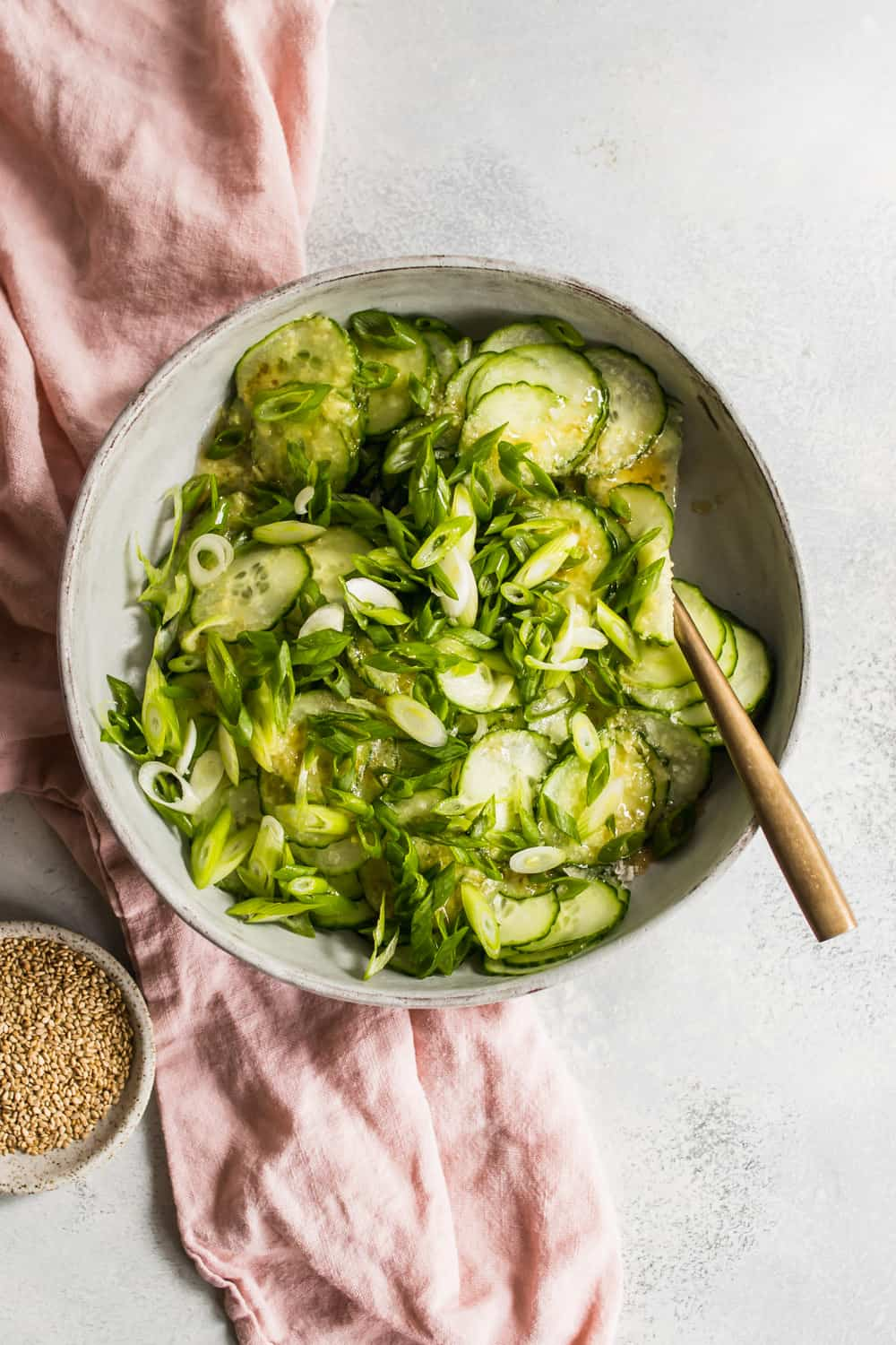 Large bowl of asian cucumber salad topped with dressing and green onions