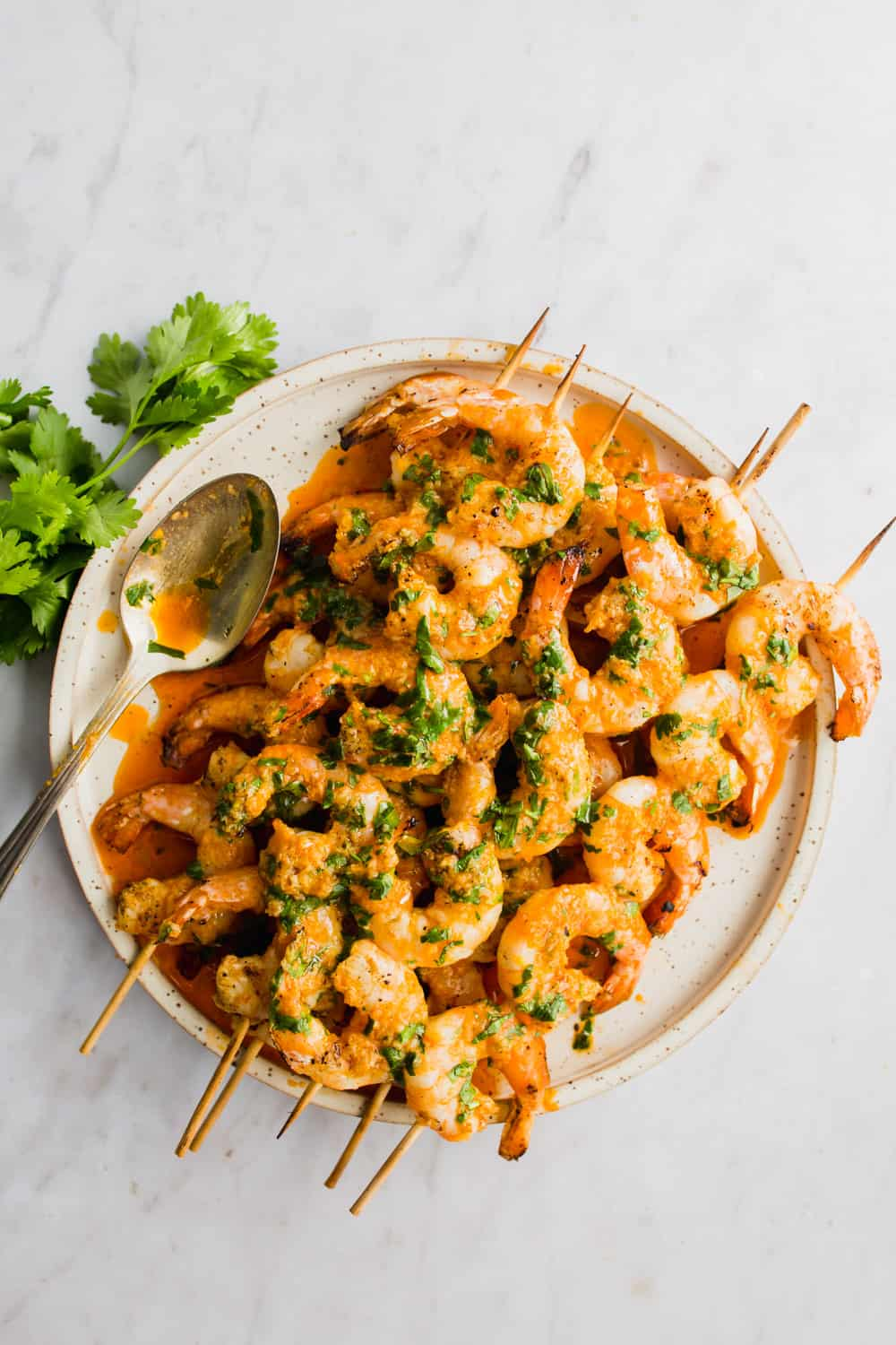 Overhead shot of orange grilled shrimp on skewers, stacked on a white plate
