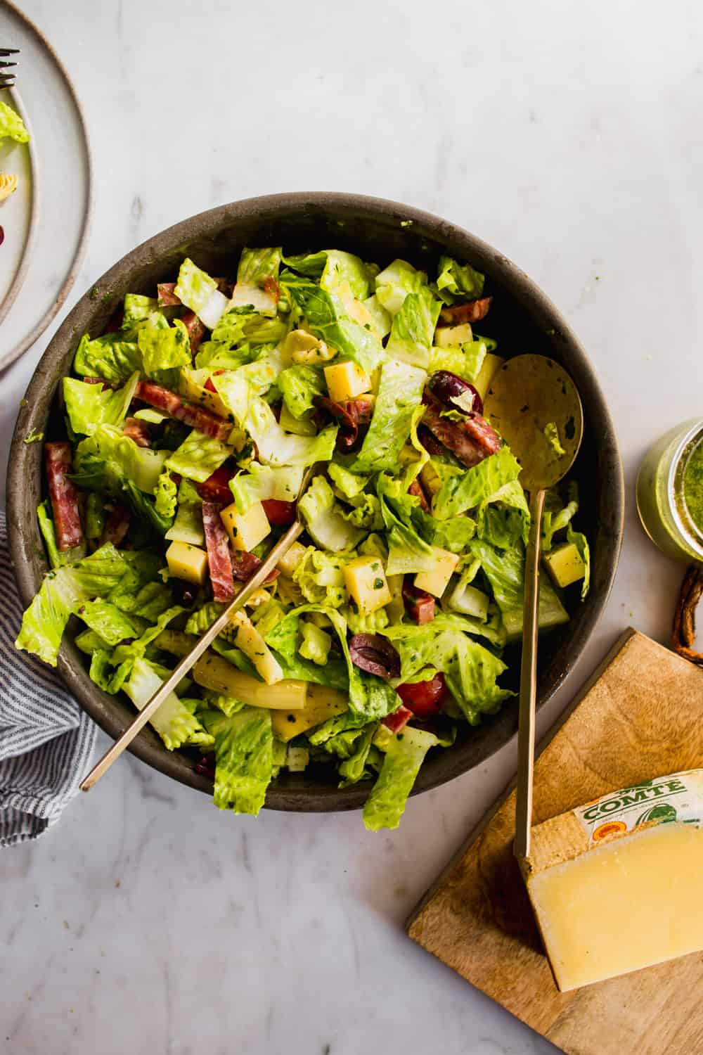 Overhead shot of a large chopped salad in a brown bowl with salad tongs