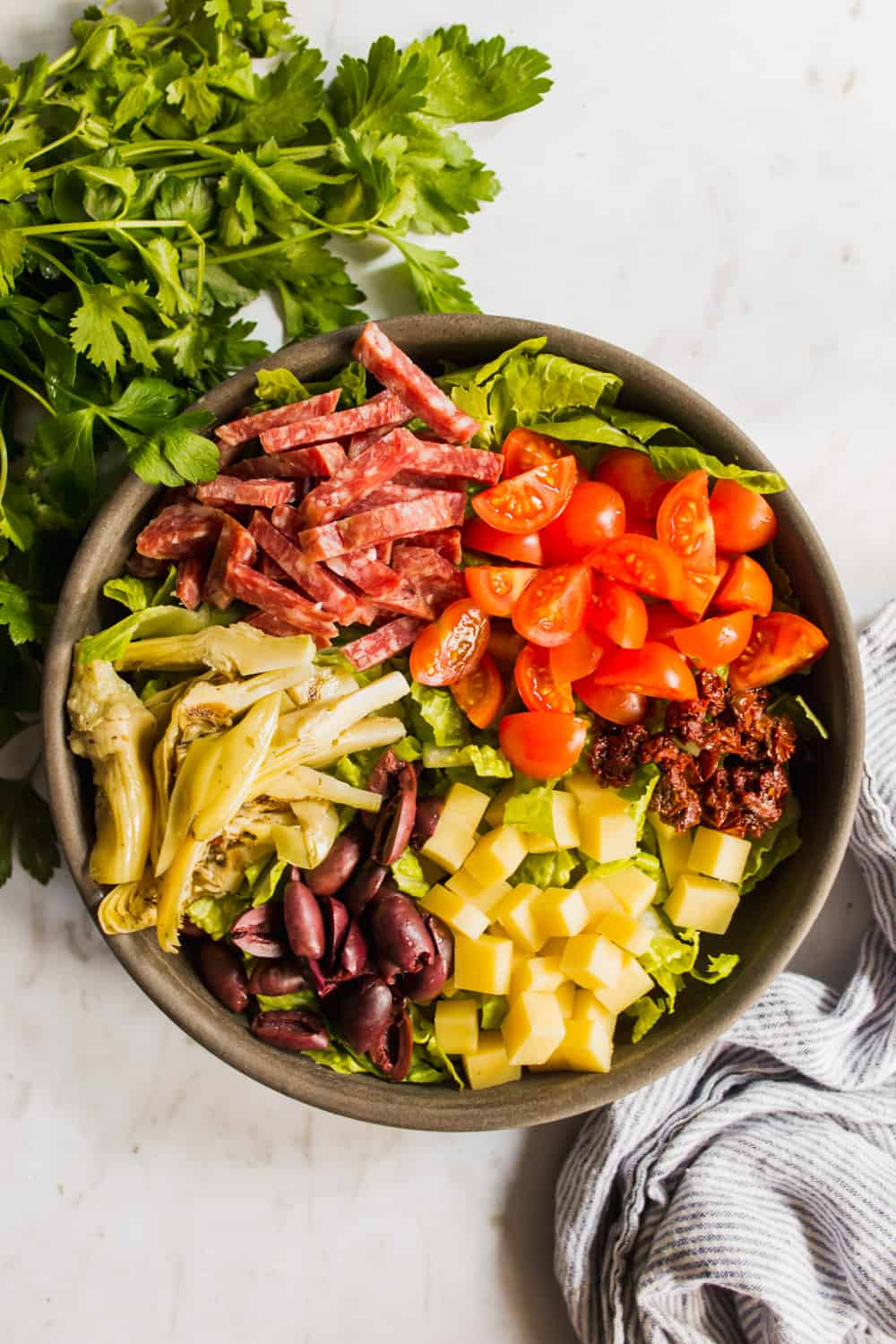 Chopped tomatoes, salami, olives, cheese, sundried tomatoes, and artichokes on top of a bowl of lettuce.