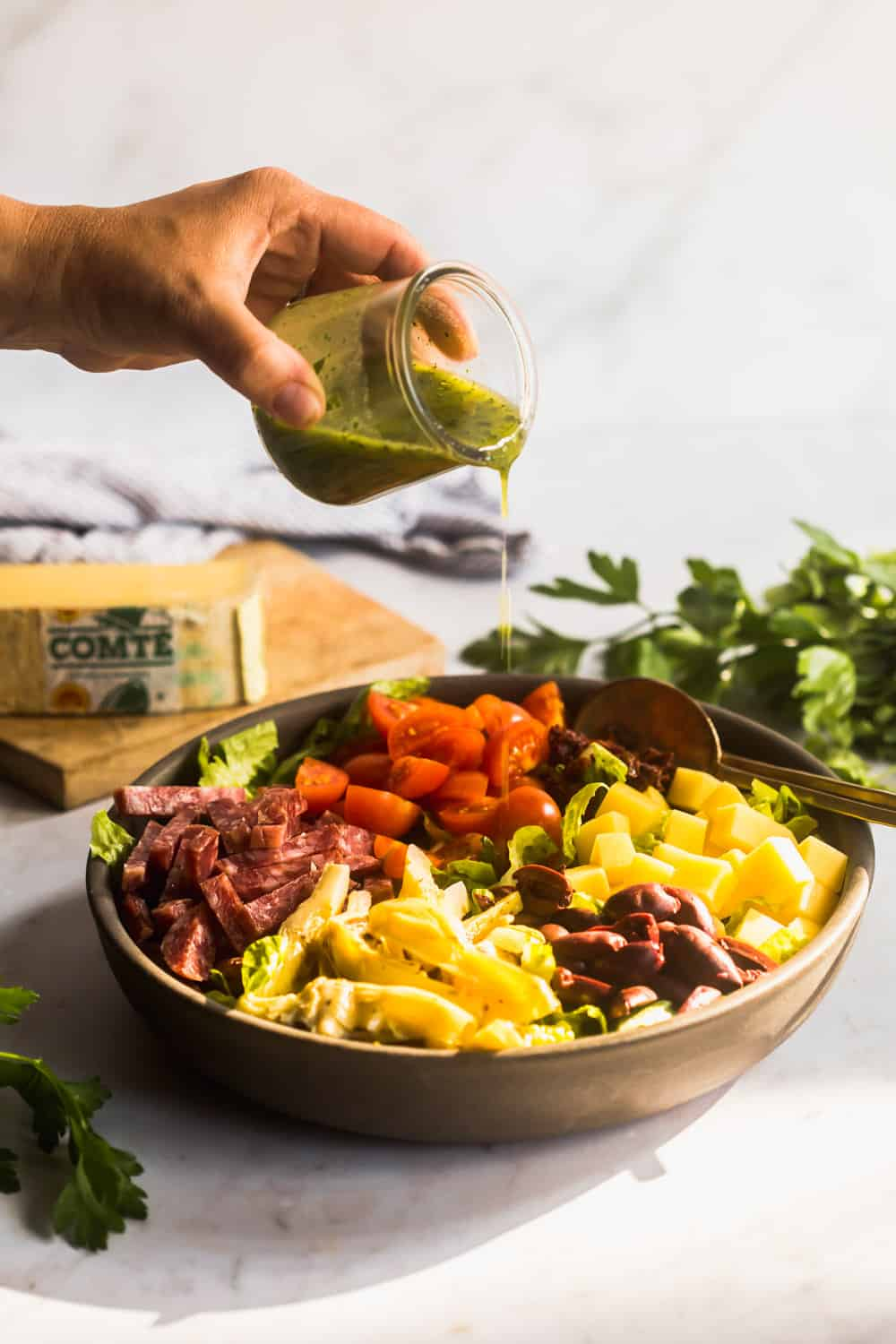 Woman's hand pouring green dressing over top a large bowl of chopped salad