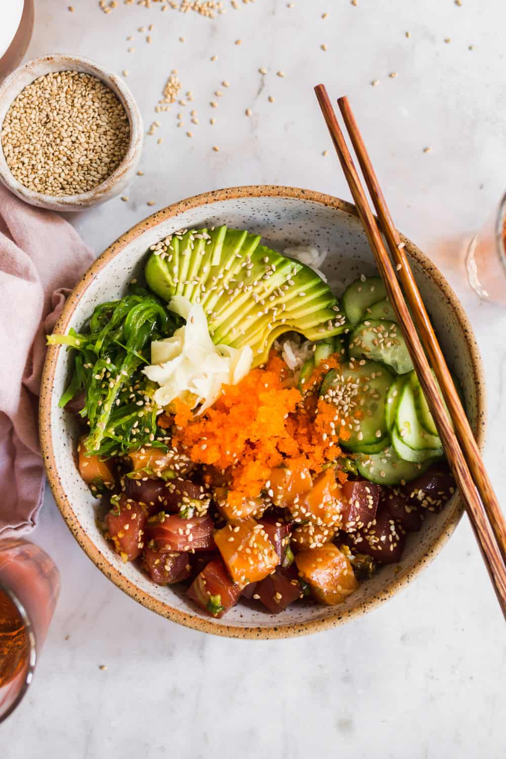 Overhead view of poke bowls with avocado, cucumber salad, raw fish, masago, ginger, and seaweed salad. Chopsticks and sesame seeds on the side.