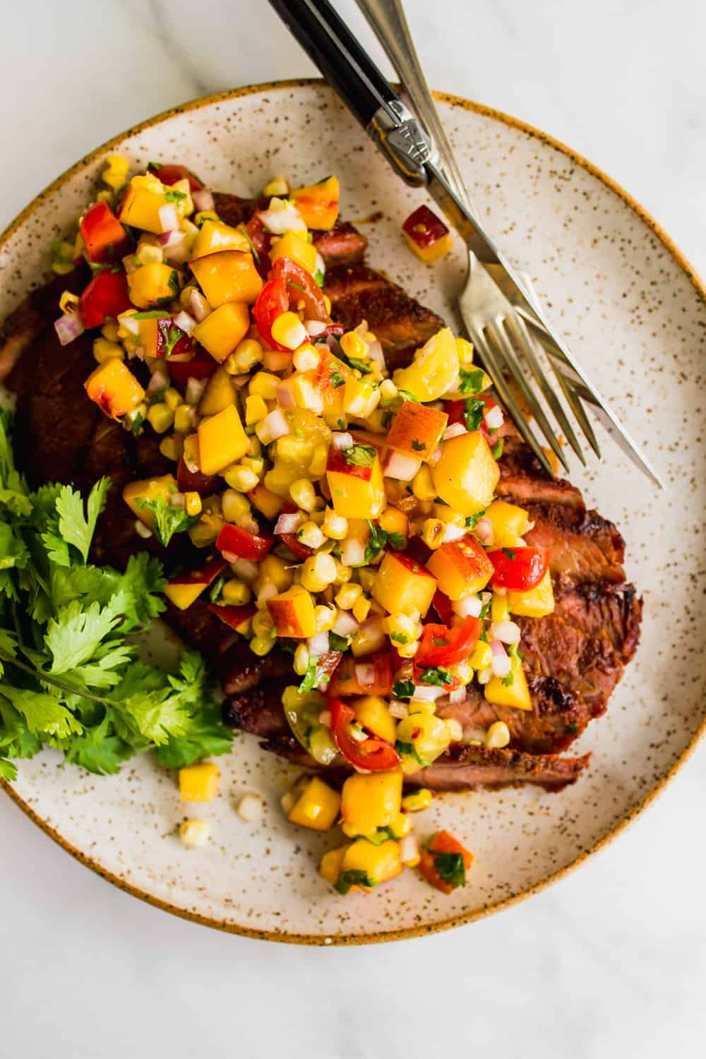 Close up of a grilled steak on a plate topped with peach salsa