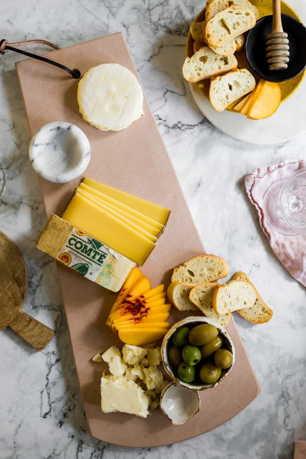 Cheese, bread, stone fruit, and olives on a pink platter.