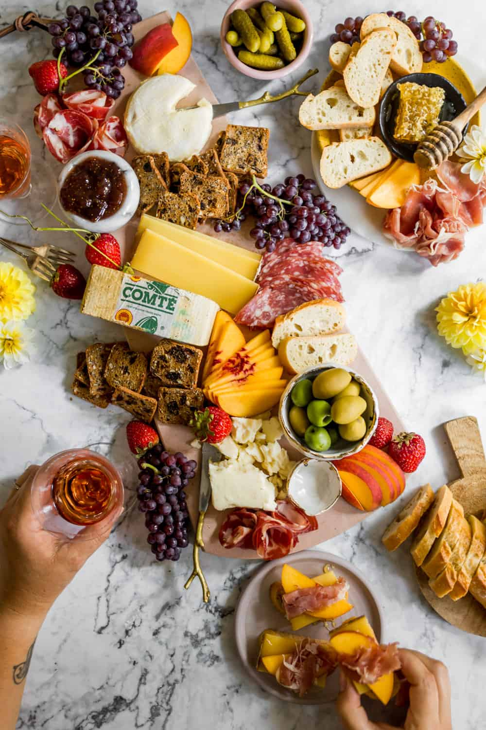 Lots of fresh summer charcuterie ingredients on platters. Woman's hands holding a drink and a cracker with cheese, fruit, and meat.