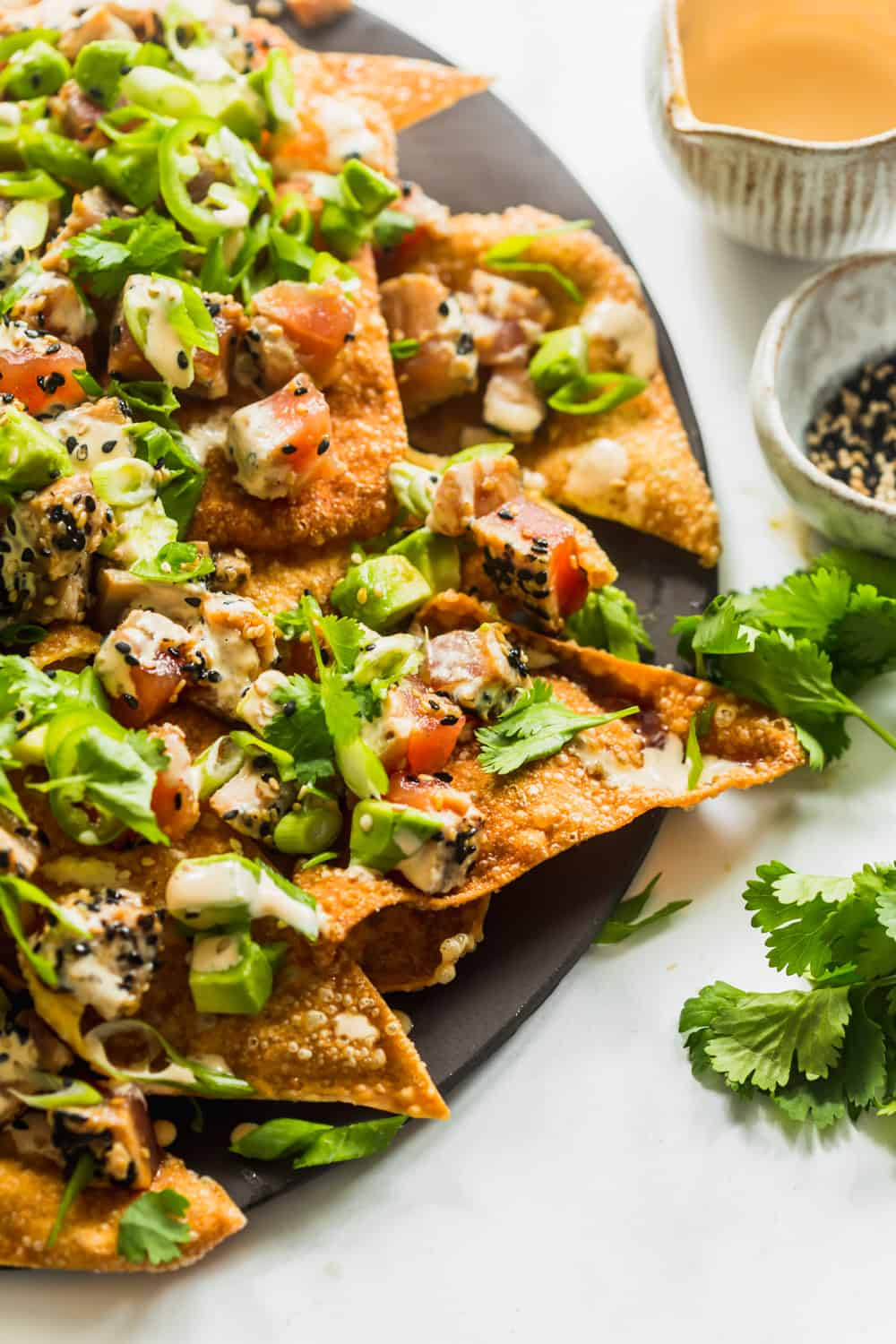 Close up of a plate of wonton nachos covered in tuna, avocado, and cilantro.