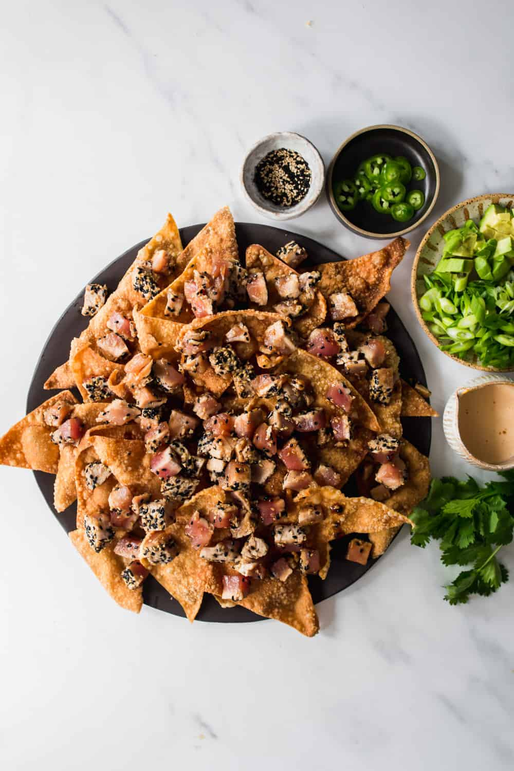 Nachos on a plate with cubes of tuna. Sesame seeds, jalapeños, green onions, and spicy mayo on the side.