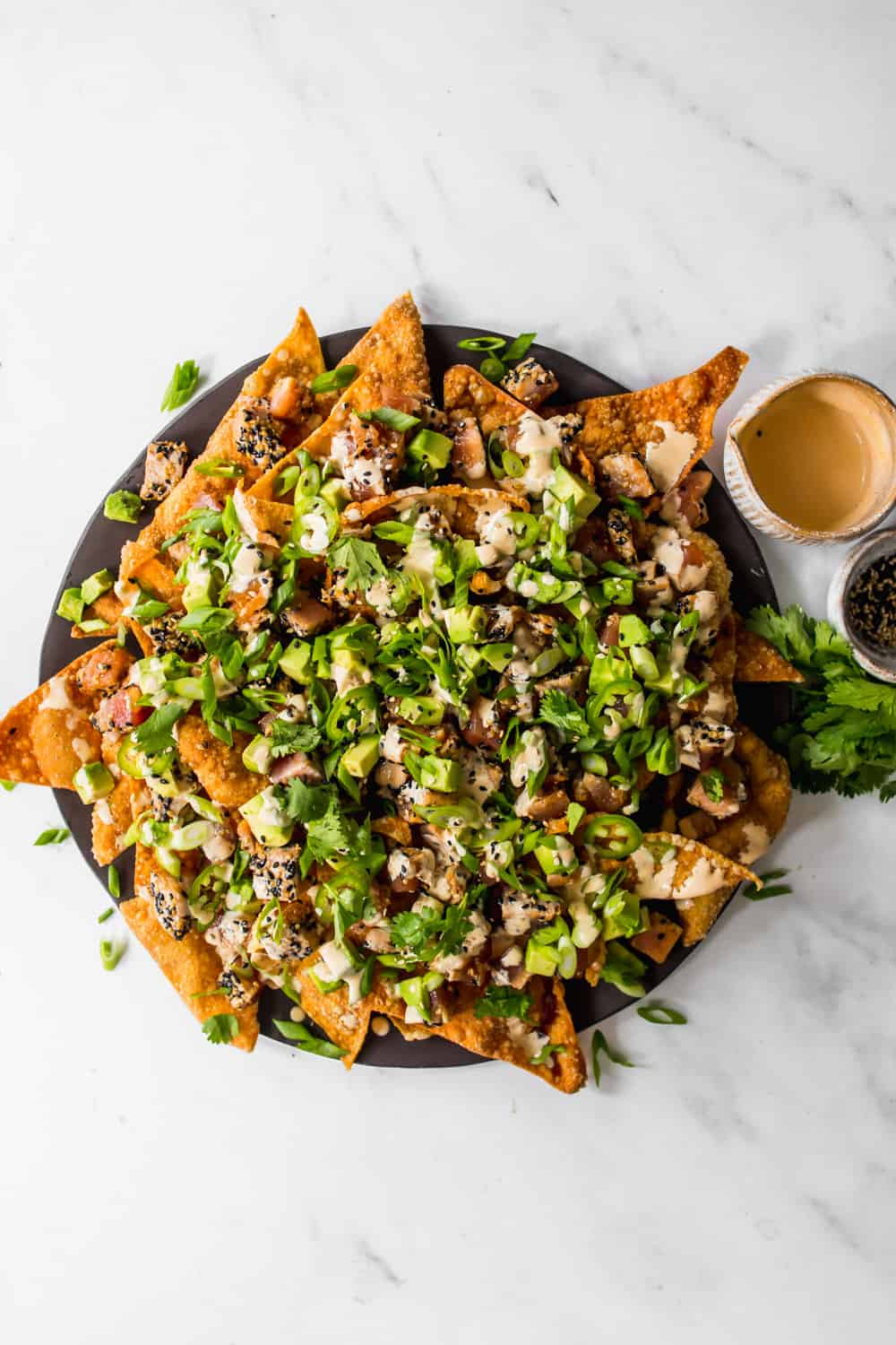 Overhead view of a plate of wonton nachos covered in green onion, cilantro, avocado, spicy mayo, and tuna.