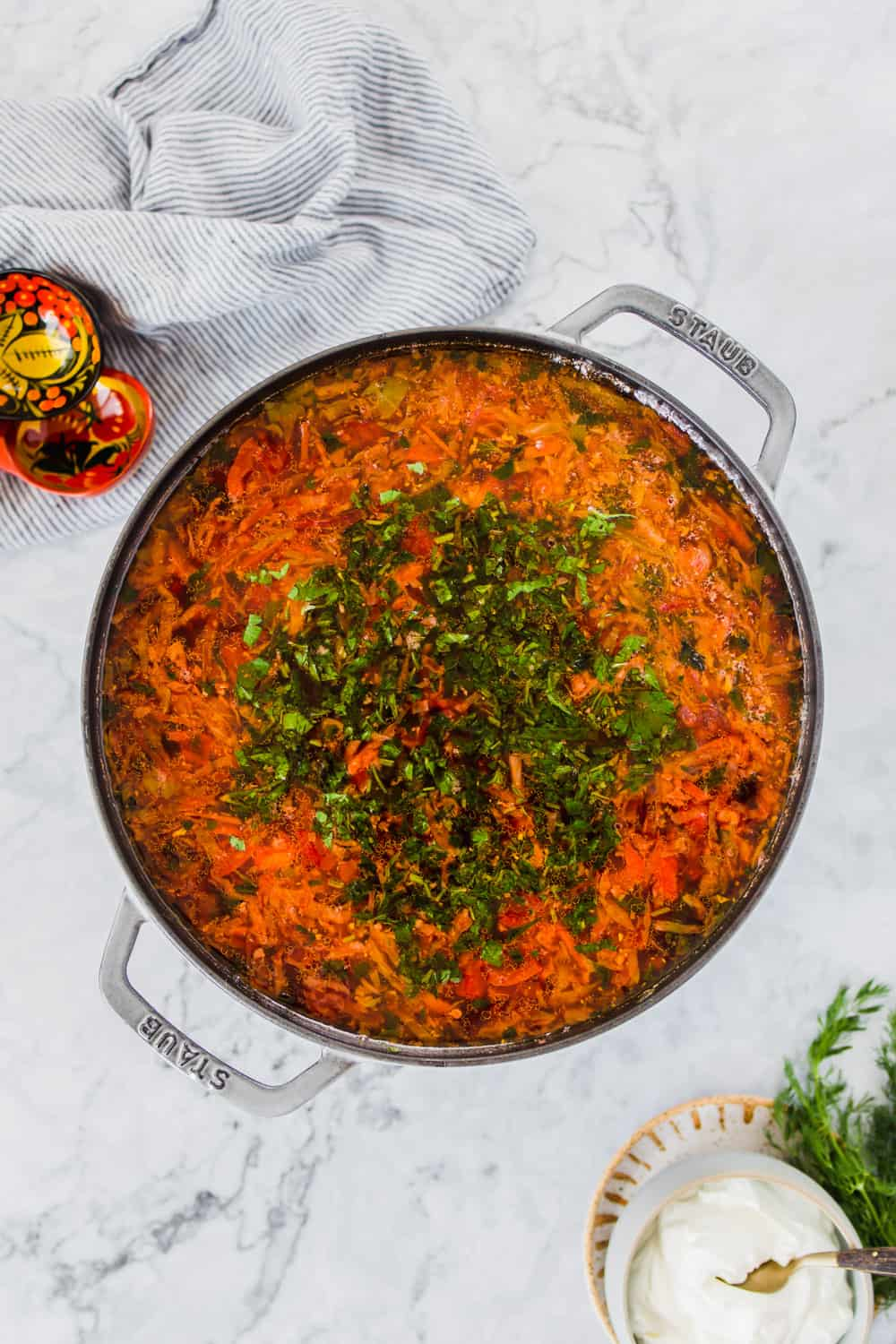 Large pot filled with orange soup and green herbs on top