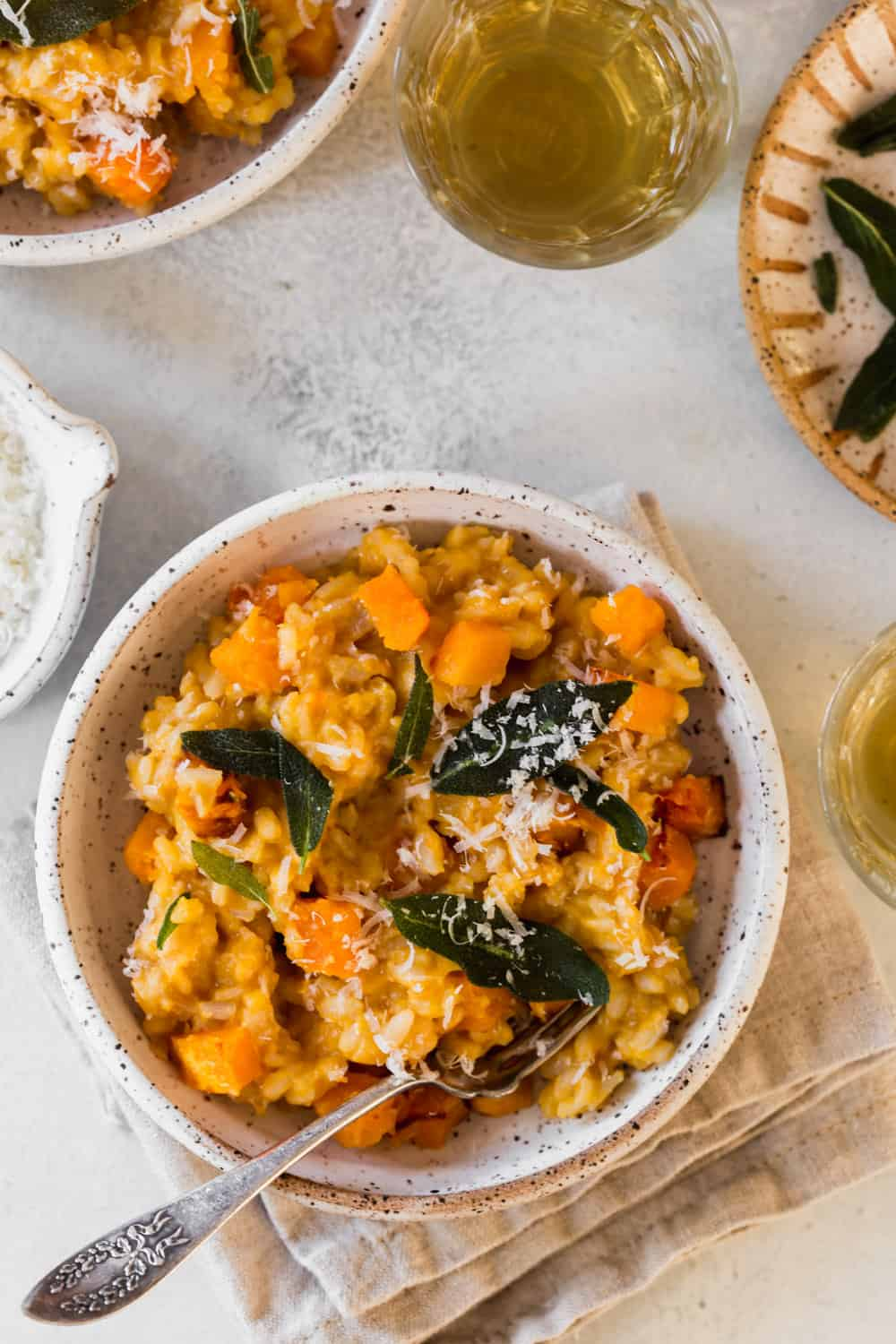 White bowl with cooked risotto with sage and cheese on top.