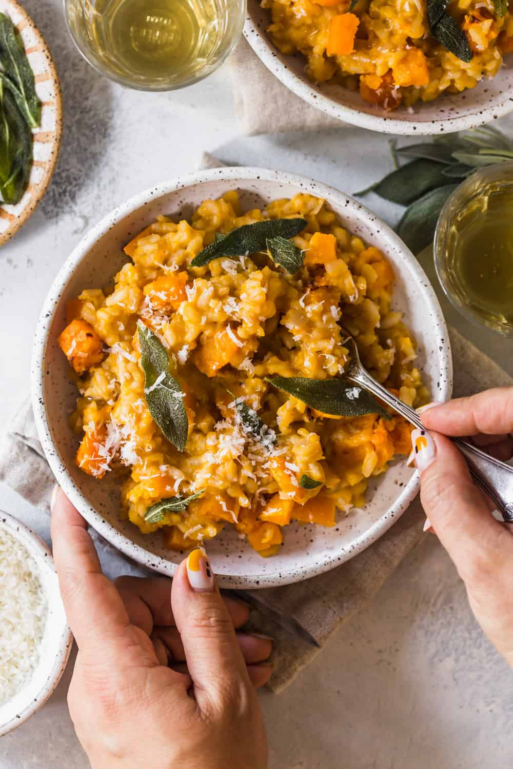 Woman's hands holding a white bowl full of cooked risotto with roasted squash and sage on top.
