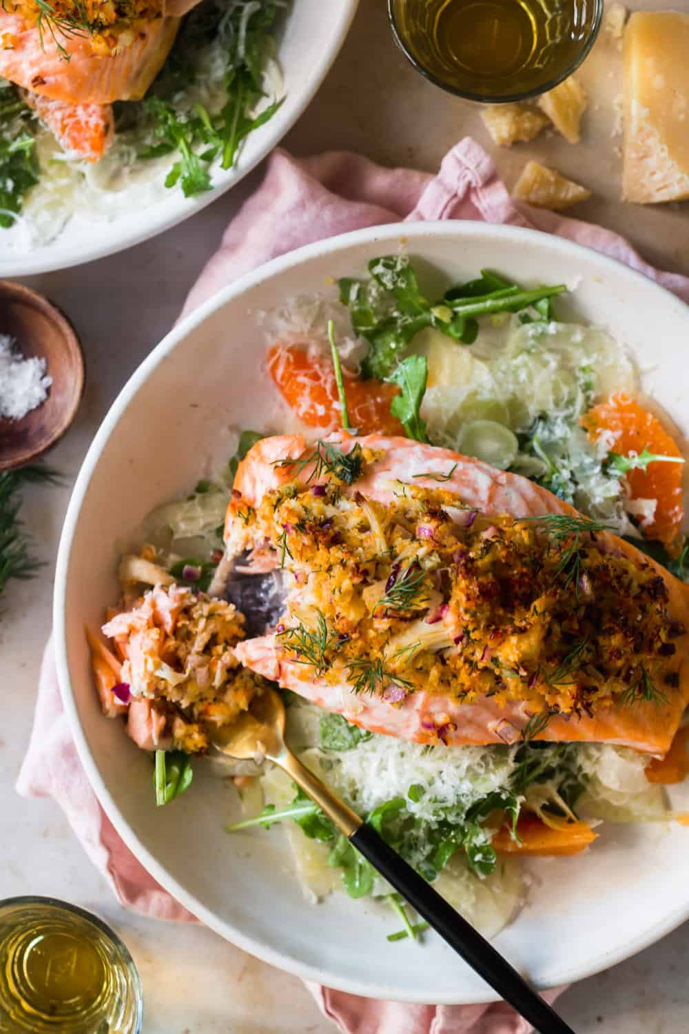 Baked stuffed salmon in a white plate on top of a green salad