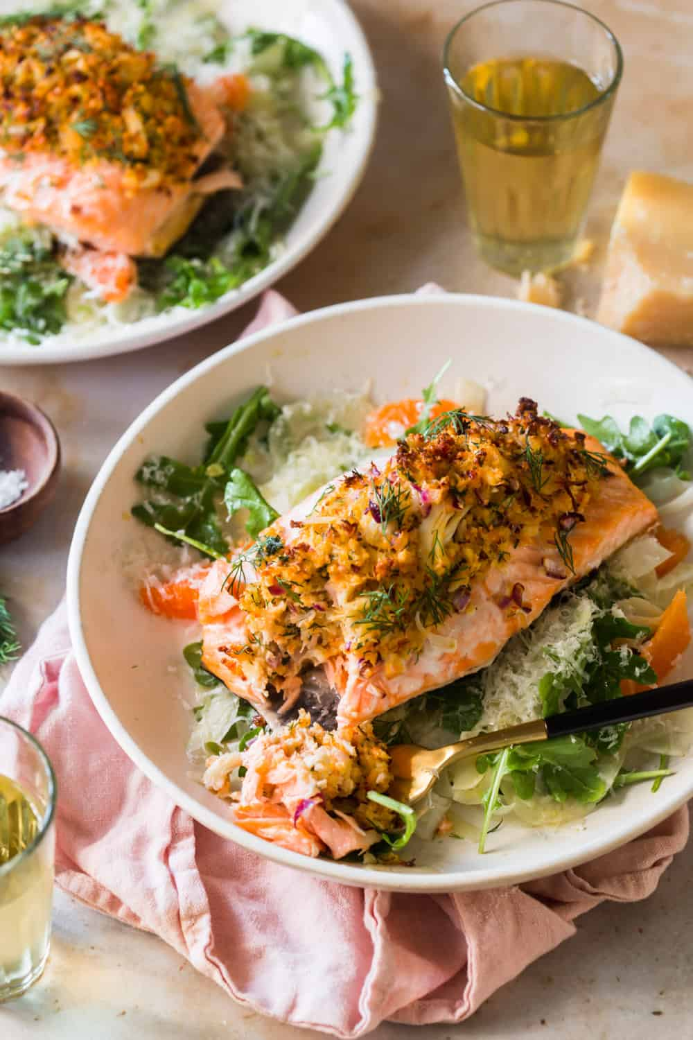 White plate with stuffed salmon on top of a green salad