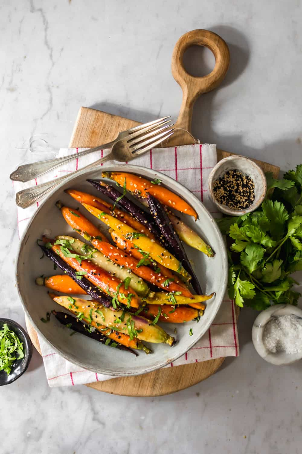 Roasted carrots in a large bowl with sesame seeds and cilantro on top.
