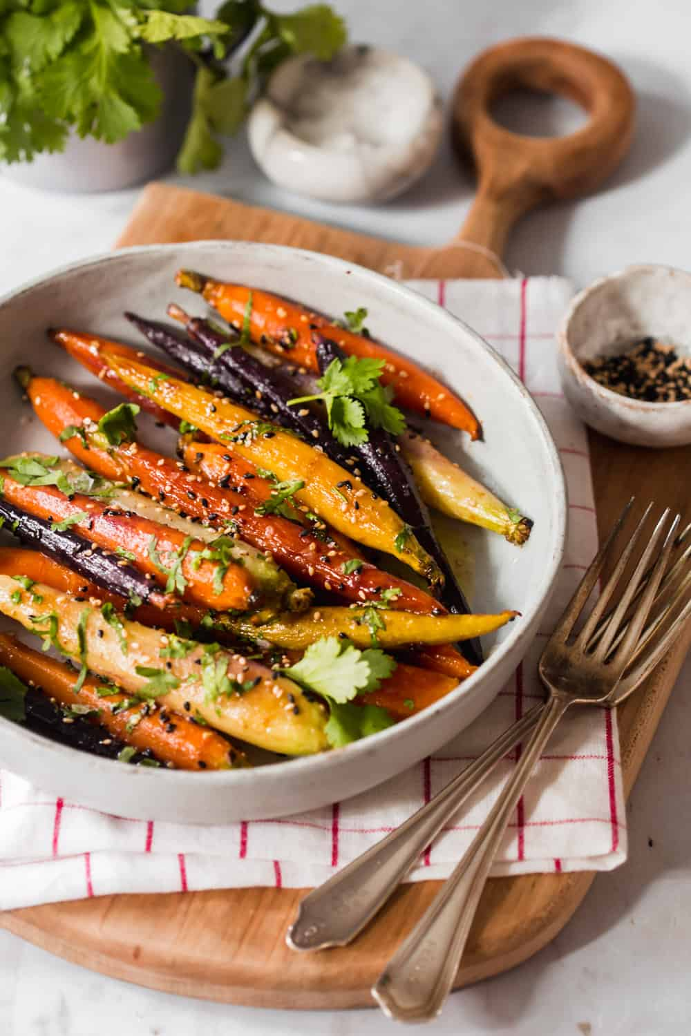 Multicolored glazed carrots in a white bowl with sesame seeds and cilantro on top.