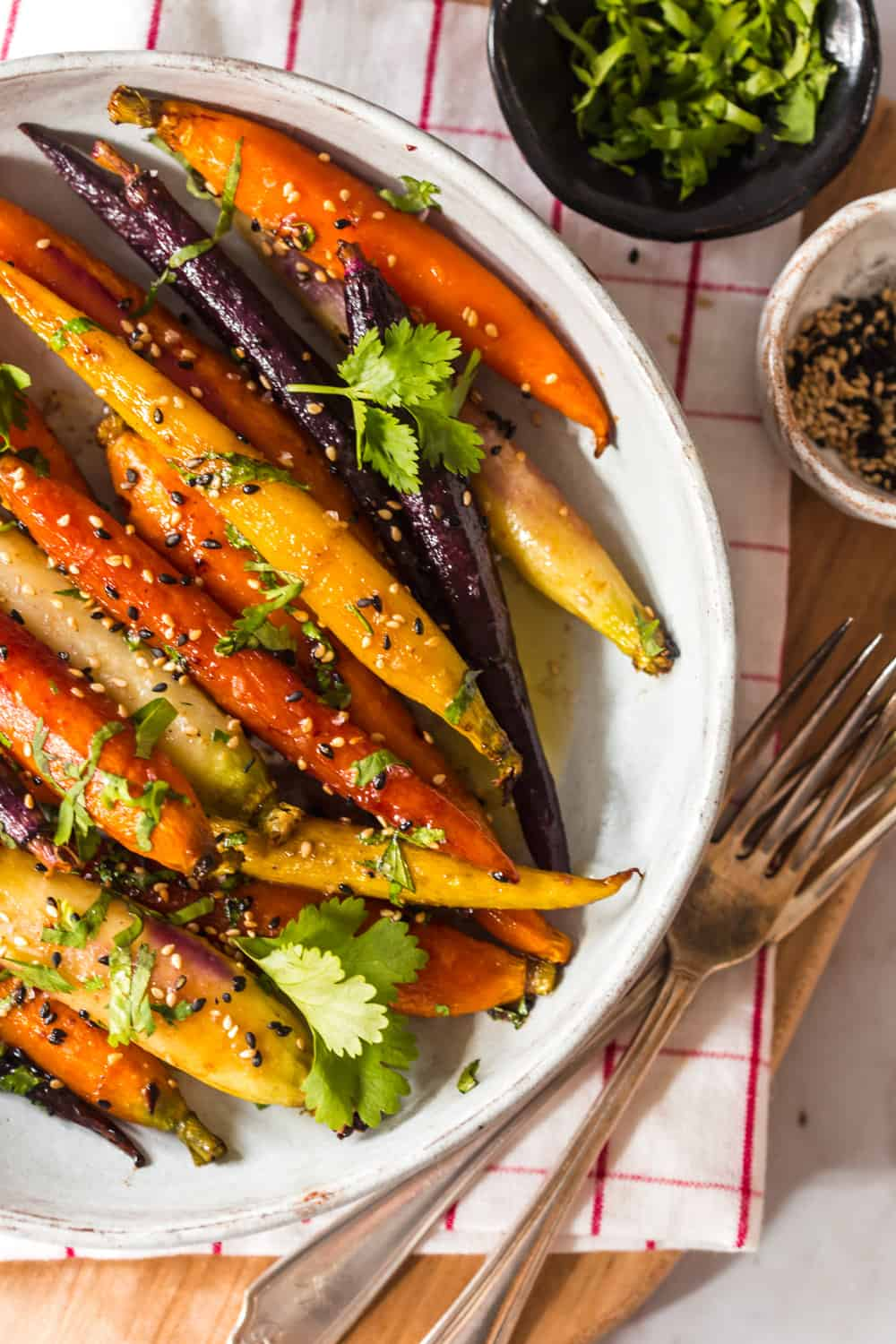 Close up of multicolored glazed carrots with sesame seeds and cilantro on top.
