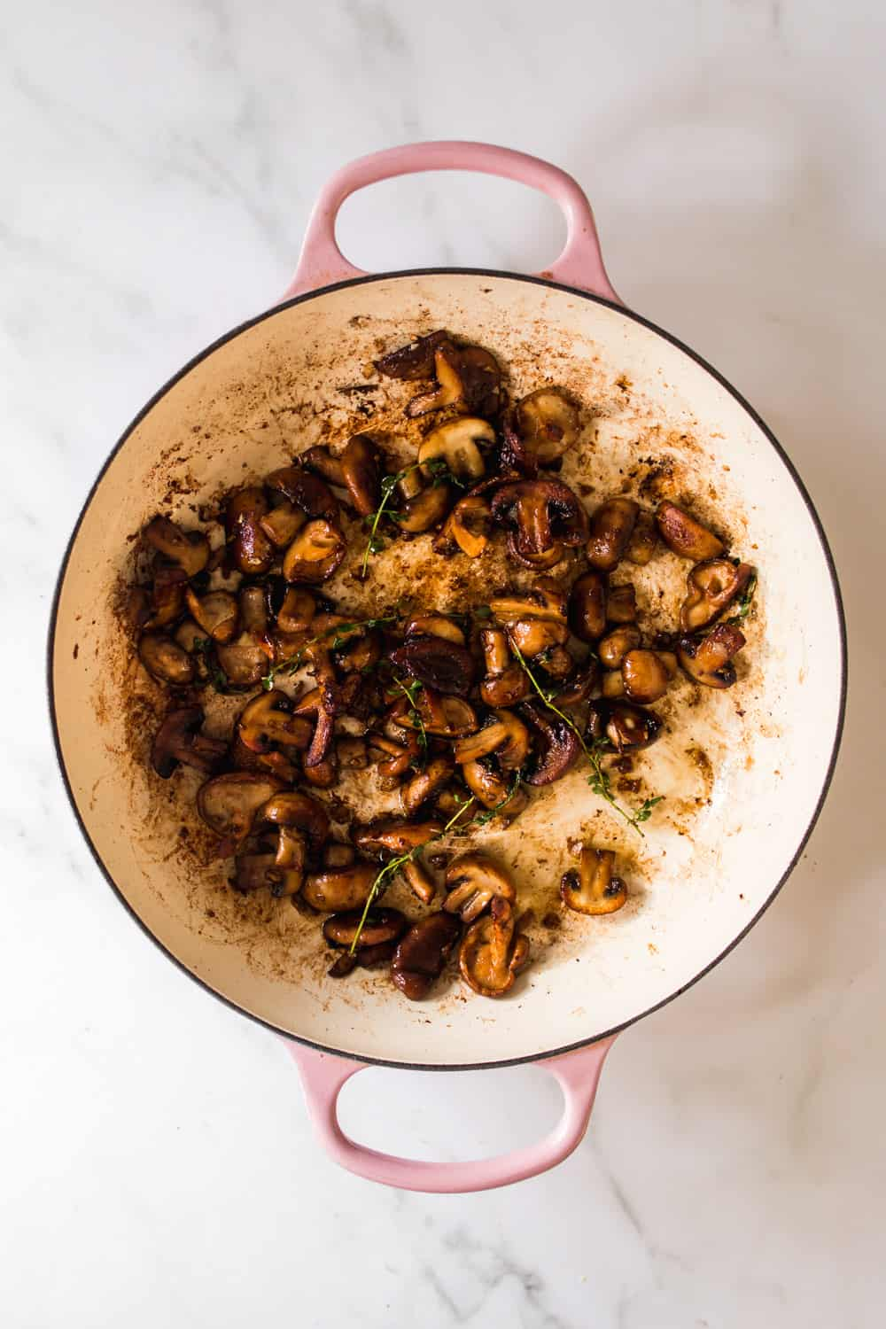 Large pot with cooked mushrooms and sprigs of thyme