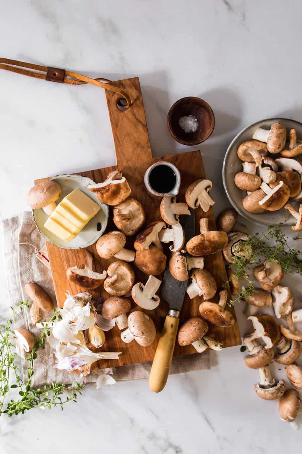 Chopped mushrooms on a cutting board. Butter and herbs on the side.